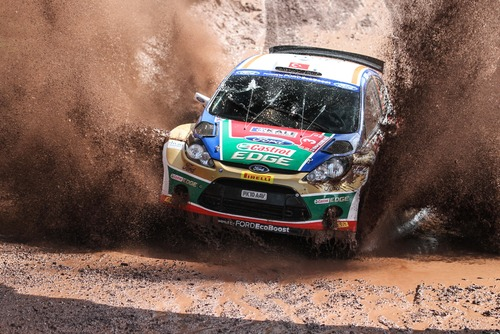 A colorful rally race car comes towards the camera in a spray of dirt